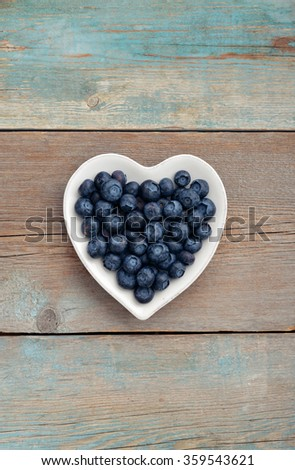 Plate in shape of heart with blueberries on wooden background, top view