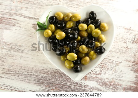 Plate in the form of heart with black and green olives on painted wooden background - stock photo