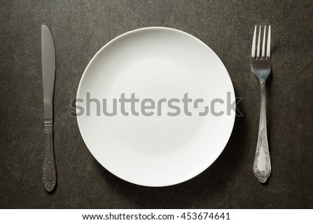 plate, knife and fork on dark background - stock photo