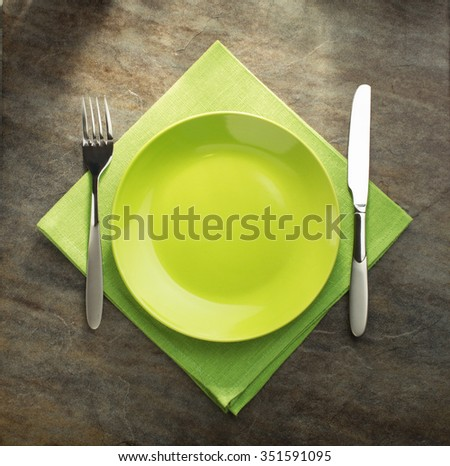 plate, knife and fork on napkin cloth - stock photo