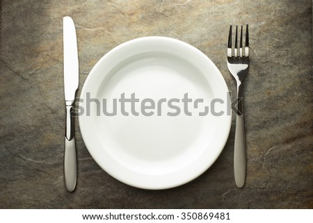 plate, knife and fork on table background - stock photo