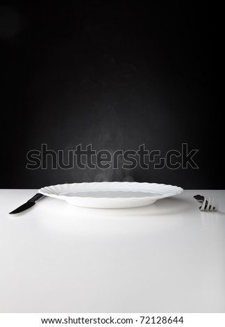 Plate, knife and fork on white and black background