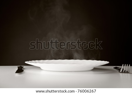 Plate, knife and fork on white and black background - stock photo