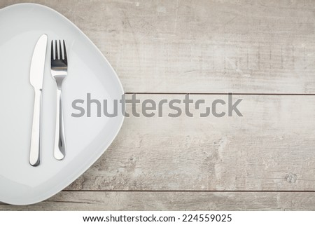 Plate knife fork. On wooden board.  - stock photo