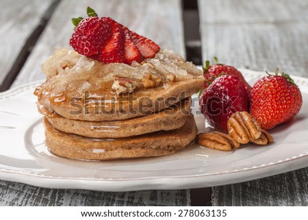 Plate of a stack of organic whole wheat pumpkin pancakes topped with apple cinnamon spiced syrup, strawberries, and pecans - stock photo