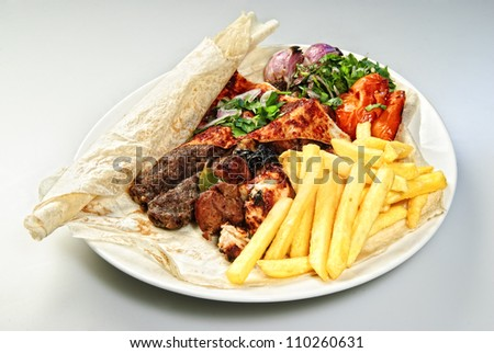 Plate of Arabic french fries with roasted meat and vegetables. - stock photo