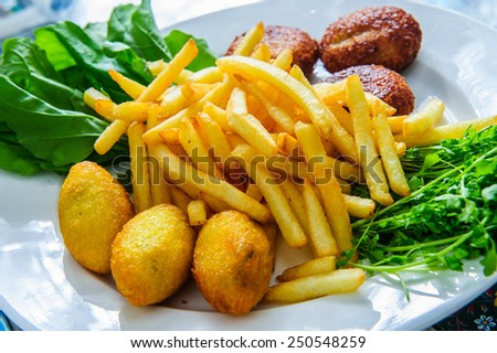 Plate of Arabic traditional falafel with french fries and greens. - stock photo