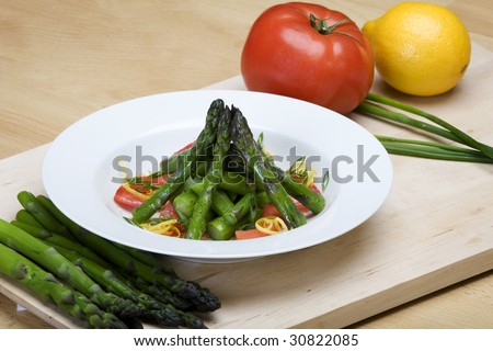 Plate of asparagus and tomato salad with fresh produce on cutting board