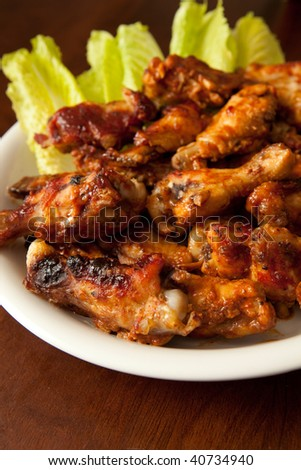 Plate of BBQ chicken wings on wood table with shallow dof - stock photo