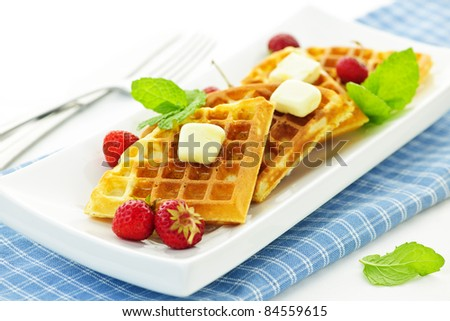 Plate of belgian waffles with fresh strawberries and pats of butter - stock photo
