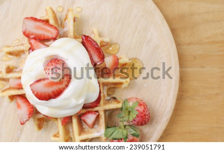 Plate of belgian waffles with fresh strawberries and whipped cream  - stock photo