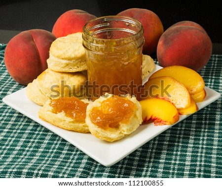 Plate of biscuits with peaches and peach jam or jelly - stock photo