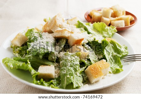 plate of caesar salad with folk and crisp breads on background