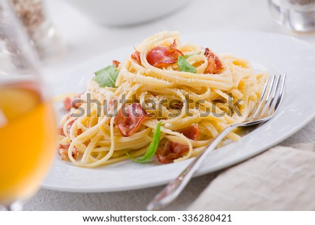 Plate of carbonara pasta with bacon and grated cheese