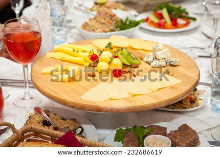 plate of cheeses and salads on the holiday table - stock photo