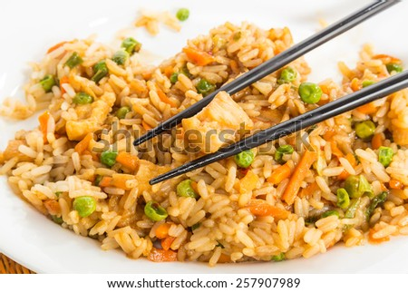 Plate of chicken fried rice with chopsticks on white plate
