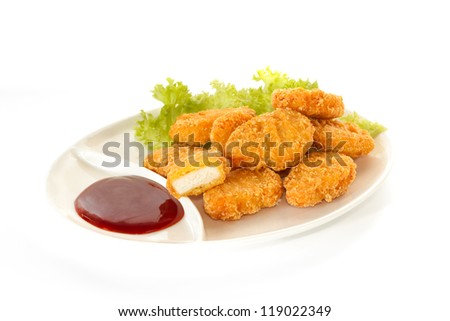 Plate of chicken nuggets with dip sauce, one nugget cut, isolated on white background - stock photo