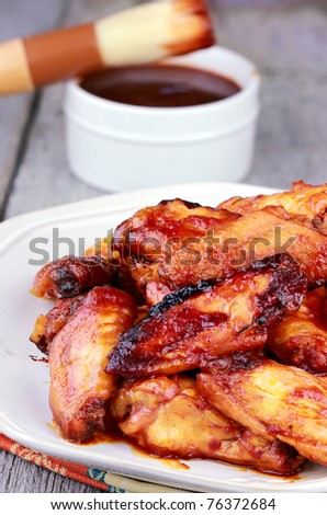 Plate of chicken wings with selective focus on chicken at the edge of plate and extreme shallow depth of field. BBQ sauce with basting brush in the background. - stock photo