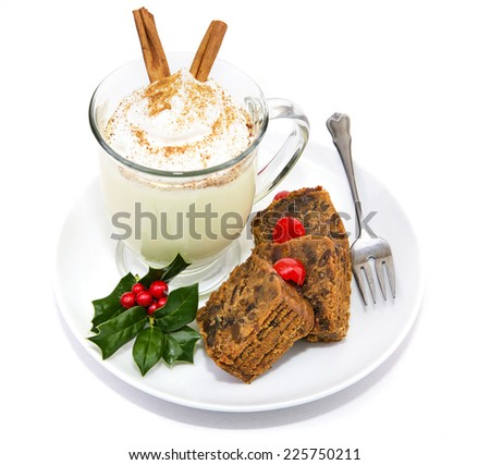 Plate of Christmas fruitcake and delicious frothy eggnog isolated on white. - stock photo