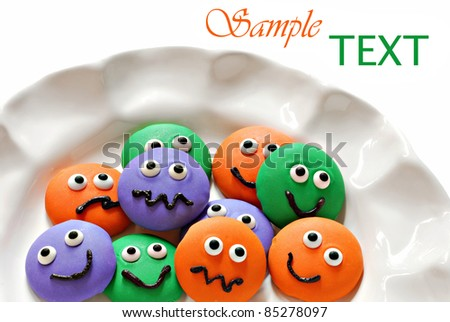 Plate of colorful little homemade cookie faces on white background with copy space.  Macro with shallow dof. - stock photo