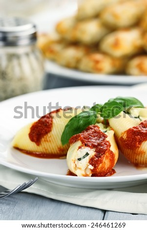 Plate of conchigliei pasta stuffed with a ricotta cheese and basil leaves with extreme shallow depth of field. - stock photo