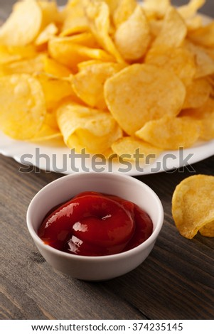 Plate of crispy chips and red sauce vertical close-up macro shot