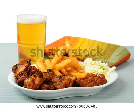 Plate of delicious barbecued chicken wings with beer. - stock photo