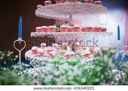 Plate of delicious colorful cupcakes on a white plate in wedding ceremony scene. - Soft focus - stock photo