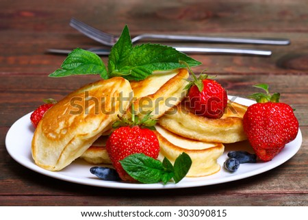 Plate of delicious freshly prepared pancakes with strawberry and jam - stock photo