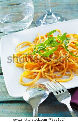Plate of delicious pasta topped with fresh herbs served ready for dining.
