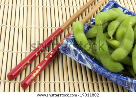 Plate of edamame with chopsticks on bamboo placemat - stock photo