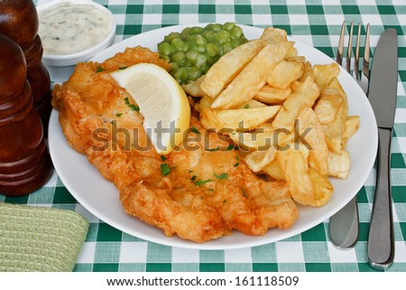 Plate of fish and chips with mushy peas and a slice of lemon on a diner table. A traditional British Seaside Dish