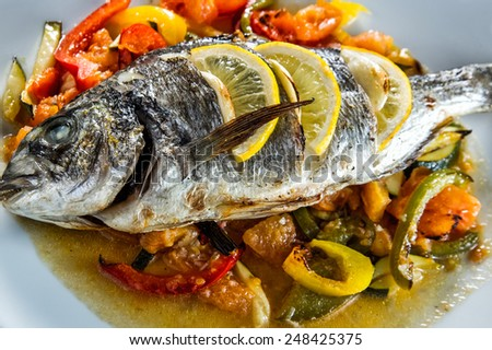 Plate of fish baked with vegetables - stock photo