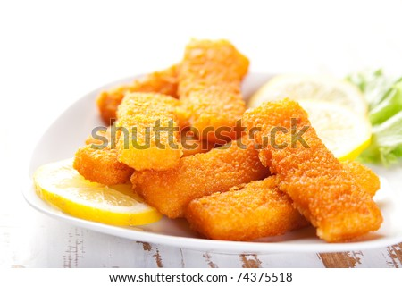 Plate of fish fingers with lemon and salad - stock photo