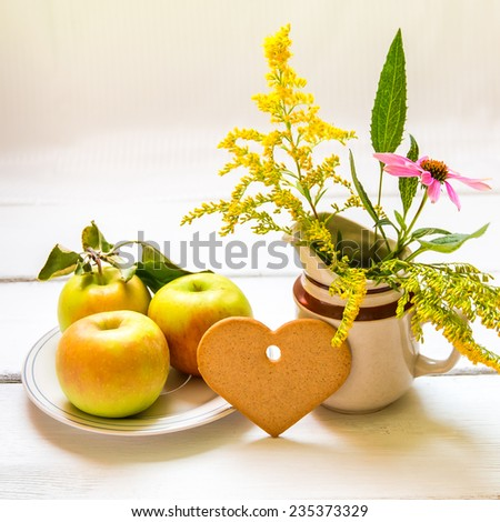 Plate of fresh apples, heart shaped cookie and  vase with wildflowers on wooden table, autumn still life. Shallow DOF. - stock photo