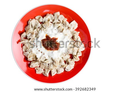 Plate of fresh homemade Turkish manti dumplings made with spicy minced lamb or beef wrapped in pasta and fried served topped with Greek yogurt and caramelised tomato sauce - stock photo
