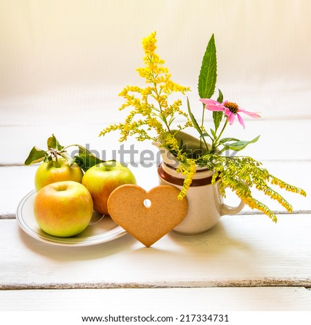 Plate of fresh  jonagold  apples, heart shaped cookie and  vase with wildflowers on wooden table, autumn still life. - stock photo