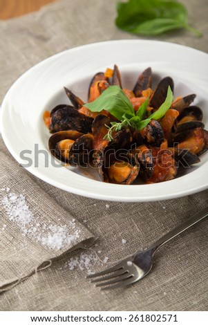Plate of fresh mussels with tomato sauce on napkin  - stock photo