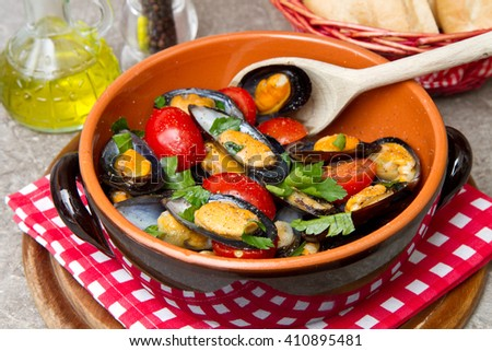 Plate of fresh mussels with tomatoes - stock photo