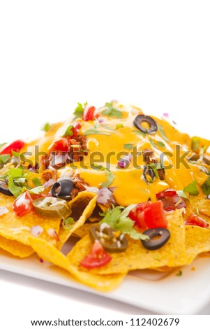 Plate of fresh nachos with a spicy jalapeno cheese sauce - stock photo