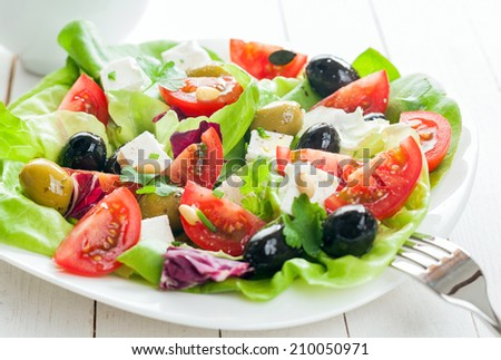 Plate of fresh salad with feta cheese, tomato , leafy greens and assorted olives on rustic white wooden boards