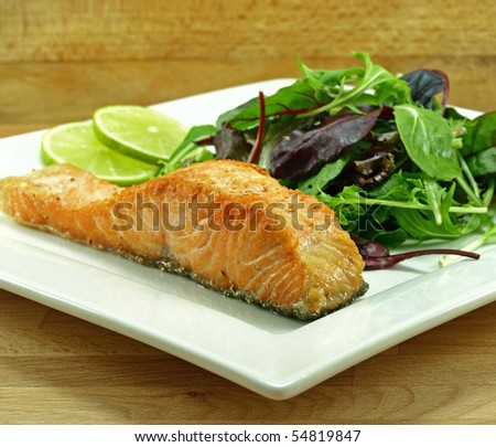 plate of freshly fried salmon fillet with baby greens - stock photo