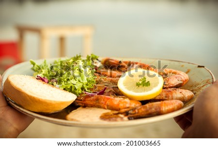 Plate of freshly grilled Shrimps with salad, lemon, and bread - stock photo