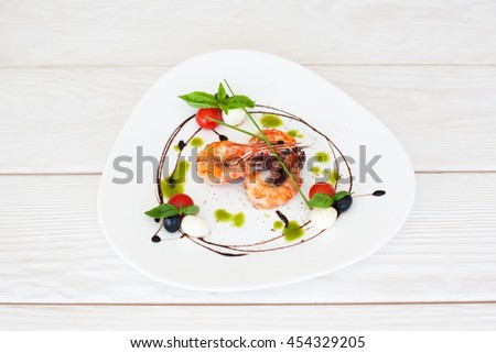 Plate of fried prawns on white wooden background, free space for text, top view on served seafood meal, photo for menu - stock photo