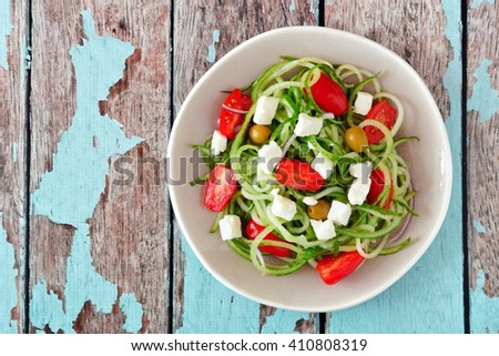 Plate of Greek Salad with cucumber noodles, overhead view on rustic wood background
