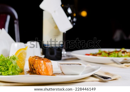 Plate of Grilled Salmon Drizzled with Sauce Served in Restaurant - stock photo
