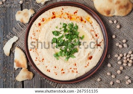 Plate of healthy hummus, creamy vegetarian food with chick-peas, paprika, olive oil and pita flatbread - stock photo