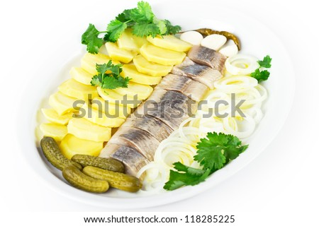 Plate of herring fish fillets with potato and onion - stock photo