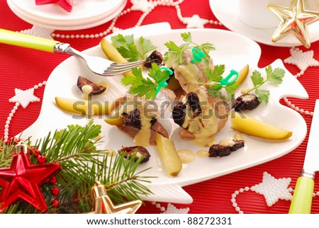 plate of herrings appetizer with prune and gherkin in mustard sauce for christmas - stock photo