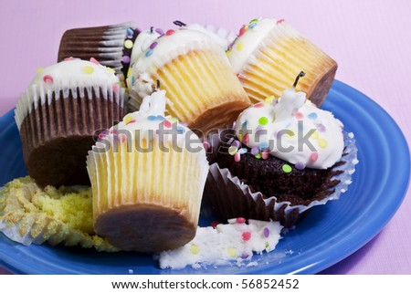 Plate of leftover cupcakes from a party over a pink background - stock photo